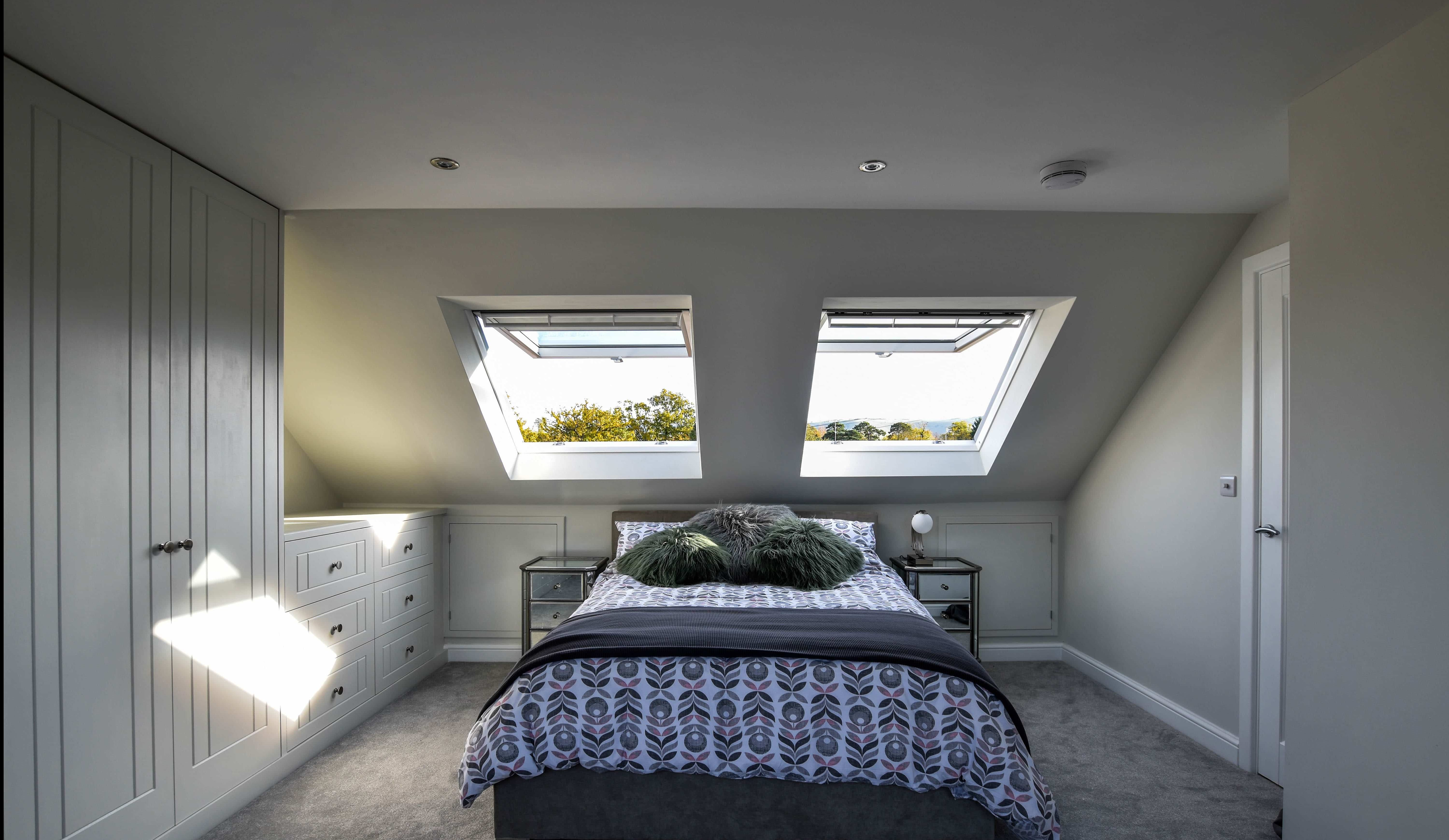 loft bedroom with large bed and two velux windows