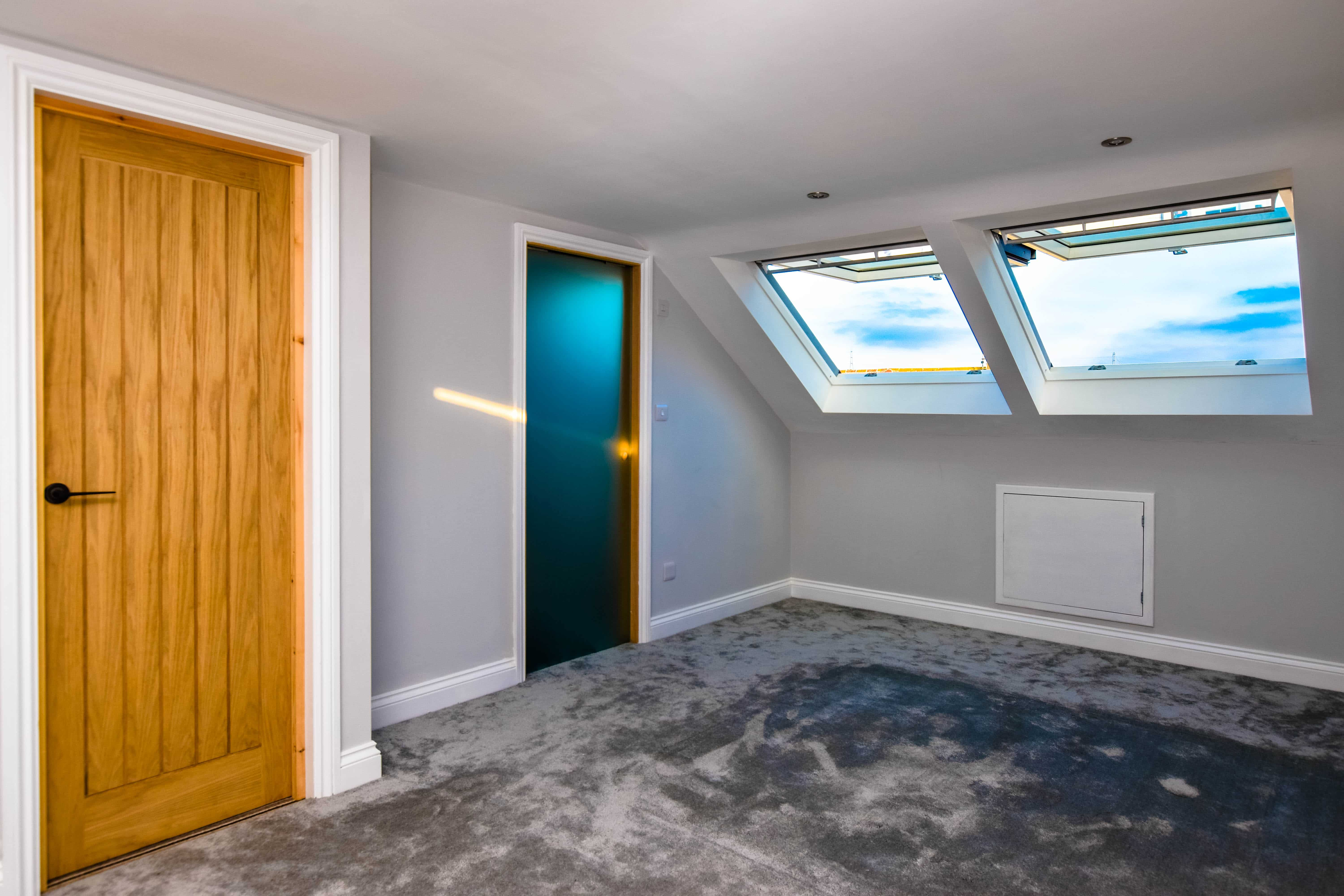 Loft conversion bedroom with two large velux windows, oak door and sliding glass door to the ensuite