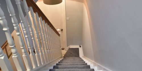 Grey carpeted staircase with turned spindles and hardwood handrails