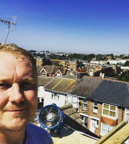 man working on the flat roof of a loft conversion with a nice view of brighton behind him